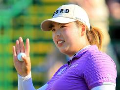 Shanshan Feng waves to the crowd after sinking a putt on 18 green during the final round of the Wegmans LPGA championship.