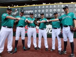 Mariners pitchers, from left, Kevin Millwood, Charlie Furbush, Stephen Pryor, Lucas Luetge, Brandon League and Tom Wilhelmsen combined to throw a no-hitter with umpire Brian Runge behind the plate.