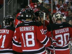 New Jersey Devils players celebrate with goalie Martin Brodeur after their Game 5 win.
