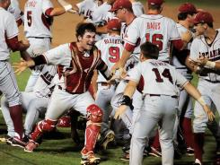 Arkansas players celebrate after defeating Baylor to advance to the CWS. It marks the program's seventh appearance.