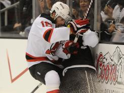 Steve Bernier of the New Jersey Devils (18) boards Rob Scuderi of the Los Angeles Kings in the first period of Game 6.