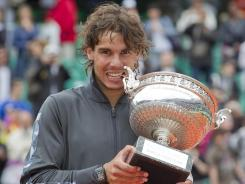 Rafael Nadal holds the trophy after completing his 6-4, 6-3, 2-6, 7-5 victory against Novak Djokovic of Serbia in the French Open final.