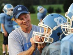Kevin Guskiewicz, a UNC professor and researcher who has been studying concussions for 18 years, is shown in 2011 helping Pop Warner League football players adjust their helmets.