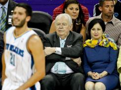 Tom Benson, center, and his wife, Gayle, watch Greivis Vasquez and the Hornets on April 15, shortly after agreeing to purchase the team from the NBA.