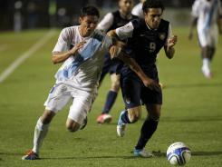 Guatemala's Carlos Gallardo, left, and Herculez Gomez, right, fight for the ball during their World Cup qualifying match.