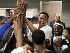 Jabari Parker celebrates with his Simeon (Chicago) teammates after winning an Illinois state super sectional basketball playoff game. Starting Friday, college coaches will be able to have unlimited text and telephone contact with Parker and other recruits who have finished their sophomore seasons.