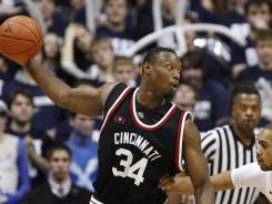 Former Cincinnati forward Yancy Gates (34) is guarded by Xavier Musketeers forward Jeff Robinson (right) during the Musketeers' win over the Bearcats during the 2011-12 season.