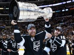 Jeff Carter holds up the Stanley Cup Monday night as teammate Mike Richards looks on.