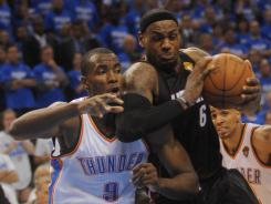 Heat forward LeBron James drives past Thunder forward Serge Ibaka on Thursday in Game 2 of the NBA Finals.