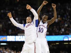 Jayhawks guard Christian Garrett, left, celebrates with guard Tyshawn Taylor after beating Ohio State in the Final Four.