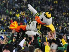 Oregon's Ducks mascot gets a lift from fans after the Pac-12's championship game last December. Oregon beat UCLA 49-31.