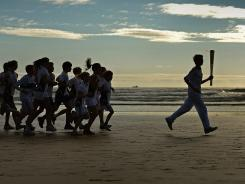 Joseph Forrester and children from Madras College run along West Sands beach with the Olympic torch on Wednesday in St Andrews, Scotland. The Olympic flame was on Day 26 of a 70-day relay.