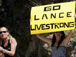 A fan holds a placard to support Lance Armstrong as she waits for riders to pass during the 12th stage of the 2010 Tour de France.