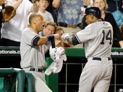 New York Yankees' Curtis Granderson celebrates with Derek Jeter after hitting a home run in the ninth inning against the Washington Nationals.