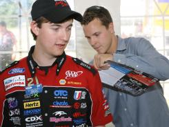 Trevor Bayne, right, signs an autograph for Auto Skills contestant Kenneth Bye on Tuesday in Dearborn, Mich.