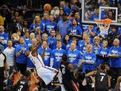 Thunder small forward Kevin Durant (35) misses a shot against agressive defense by Heat small forward LeBron James (6) at the end of the fourth quarter of Game 2 in the NBA Finals.