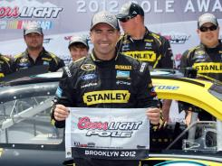 Marcos Ambrose won the pole position Saturday with a 203.241-mph lap that shattered Ryan Newman's previous mark of 194.232 mph in June 2005.