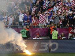 Croatian fans cheer after a flare was thrown onto the field during the Group C match between Italy and Croatia. UEFA is charging Croatia with improper conduct of supporters, including racist chants and racist symbols during the match.