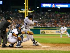 Wilin Rosario of the Colorado Rockies hits a 10th inning base hit to score two runs against the Detroit Tigers at Comerica Park.