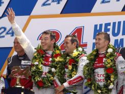 From left, German Andre Lotterer, Frenchman Benoit Treluyer and Swiss Marcel Fassler celebrate on the podium after Audi's win at the 80th edition of the Le Mans 24-hour endurance race.