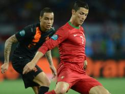Dutch defender Gregory van der Wiel, left, vies with Portuguese forward Cristiano Ronaldo during their Euro 2012 match. Ronaldo finished the match with two goals.