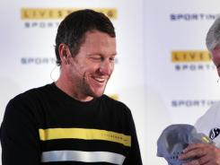 Lance Armstrong, left, gives a Livestrong hat to Sporting Kansas City owner Cliff Illig during an MLS news conference in Kansas City, Kan., on March 8.