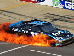 Denny Hamlin's No. 11 Toyota goes up in flames on pit road after he crashed during Sunday's race at Michigan International Speedway.