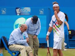 A concerned David Nalbandian checks line judge Andrew McDougall after kicking the small barrier surrounding the linesman in anger during the final against Marin Cilic.