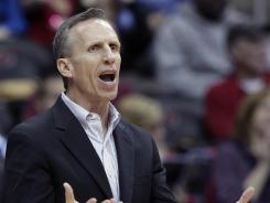 St. John's assistant coach Mike Dunlap was hired by the Charlotte Bobcats on Monday, The Charlotte Observer reported.