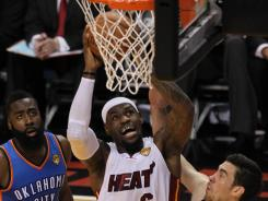 Heat forward LeBron James goes to the basket over Thunder defenders James Harden, left, and Nick Collison on Tuesday in Game 4 of the NBA Finals.