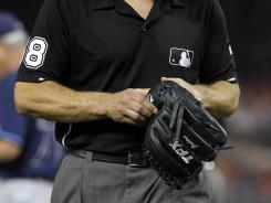 Umpire Chris Guccione examines the glove of Rays reliever Joel Peralta, who was ejected for having a foreign substance in it.