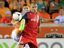 Houston Dynamo's Geoff Cameron, left, is caught up with Toronto FC's Danny Koevermans, right, as he fights for possession of the ball during the second half.