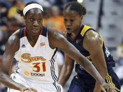 Connecticut Sun's Tina Charles is pursued by Indiana Fever's Tamika Catchings during the second half of a WNBA basketball game in Uncasville, Conn. The Sun won in overtime 88-85.