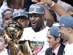 Miami Heat forward LeBron James (6) holds up the Larry O'Brien Trophy after winning the 2012 NBA championship at the American Airlines Arena. Miami won 121-106.