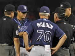 Inspection process: Joel Peralta, center, has his glove confiscated by umpires Tuesday.