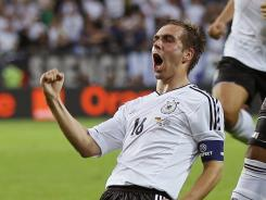 Germany captain Philipp Lahm, left, celebrates after scoring the game's opening goal. Greece equalized in the 55th minute, but Germany answered with three goals in the second half en route to the 4-2 win.