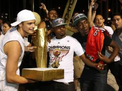 Heat fans hoist mock trophies outside AmericanAirlines Arena after the Game 5 victory Thursday.