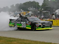 Nelson Piquet Jr. does a burnout to celebrate his victory in the NASCAR Nationwide Series Sargento 200 at Road America in Elkhart Lake, Wis.