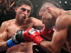 Josesito Lopez, left, lands a left hook on Victor Ortiz's jaw during their welterweight fight Saturday night at Staples Center in Los Angeles. Lopez won after breaking Ortiz's jaw.