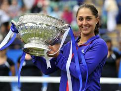 Austria's Tamira Paszek poses with her trophy after outlasting Angelique Kerber in the final at Eastbourne.