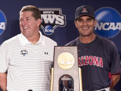 South Carolina coach Ray Tanner, left, and Arizona coach Andy Lopez pose for a photo with the national championship trophy at a press conference on Saturday.