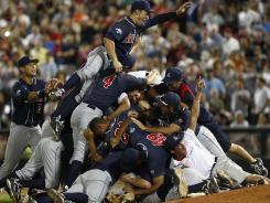 Pile of champions: Arizona players celebrate after defeating South Carolina 4-1 Monday for a sweep of the College World Series finals.