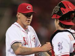 Cincinnati starting pitcher Mat Latos is congratulated by catcher Ryan Hanigan after pitching a complete game against the Milwaukee Brewers.