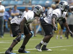 Carolina Panthers linebackers Thomas Davis, left, and Jon Beason, right, lineup during practice Thursday, June 14, 2012.