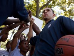Austin Rivers huddles with kids Wednesday after playing basketball at the Dunlevy Milbank Boys & Girls Club in Harlem at a pre-NBA draft event.