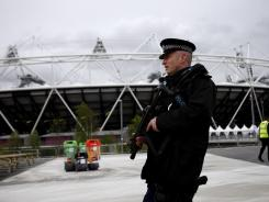 Unfamiliar sight: Armed police patrol outside Olympic Stadium in London's Olympic Park.