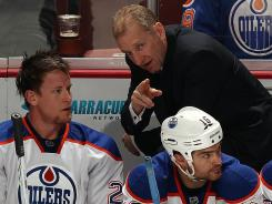 Ralph Krueger gives instructions to Edmonton Oilers defenseman Andy Sutton during a game in March.