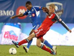 Patrice Bernier (8) of the Montreal Impact battles for the ball with Nick Soolsma (18) of the Toronto FC.