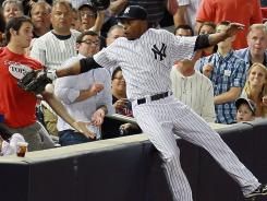 Something's amiss:  The Yankees' Dewayne Wise falls into the stands Tuesday on his non-catch that was ruled an out.