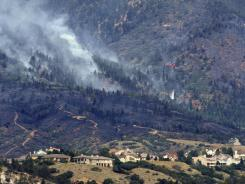 Helicopters make water drops on the Waldo Canyon Fire on Blodgett Open Space above Colorado Springs, Colo., on Thursday. Colorado Springs officials said Thursday that hundreds of homes have been destroyed by a raging wildfire that has encroached on the state's second-largest city and threatened the U.S. Air Force Academy.